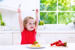 Kids eat pasta. Healthy lunch for children. Toddler kid eating spaghetti Bolognese in a white kitchen at home. Preschooler child cooking noodles with tomato and pepper for dinner. Food for family.
