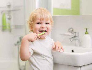 Happy kid brushing teeth